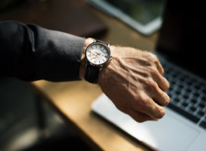 hand with watch over a laptop