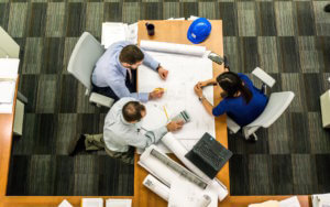 three diverse professionals working on a project around a table