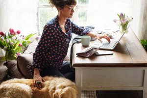 professional woman working on hr investments at home with dog