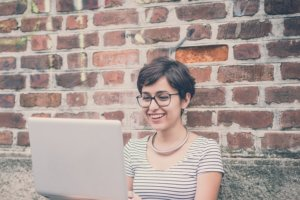 woman on laptop smiling after employee performance review
