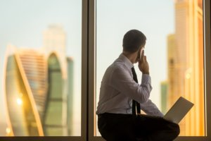 busy hr professional looking out window at city skyline
