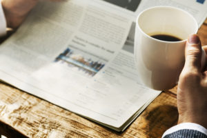 hands holding newspaper and coffee at desk