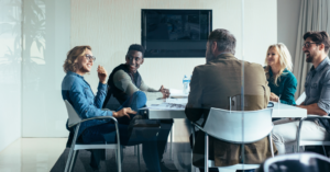Co workers sitting around table in conference room