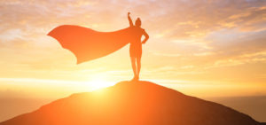 WOman standing on hill t sunset with superman cape