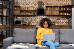 Black woman sitting on a couch on her computer.