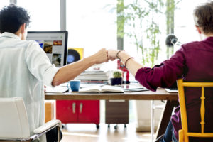 Unique sales team fist bumping eachother after a sale