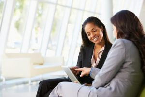 Two female customer success consultants working together to align their sales and marketing teams.